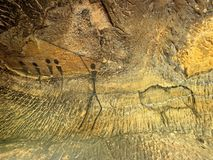 Buffalo hunting. Paint of human hunting on sandstone wall, prehistoric picture. Black carbon abstract Stock Photo
