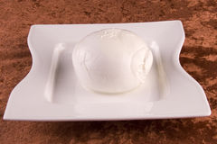 Buffalo mozzarella cheese. A view of a large ball of buffalo mozzarella cheese in a white pan, made from water buffalo milk stock photo
