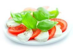 Buffalo mozzarella and tomato salad with fresh, green basil leaves. Mozzarella and tomato salad with fresh, green basil leaves and ground pepper grains Stock Photography