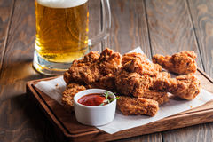 Buffalo style chicken wings. Served with cold beer on wooden background royalty free stock photo