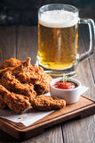 Buffalo style chicken wings. Served with cold beer on wooden background royalty free stock photos