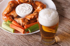Buffalo wings and beer on the table close-up horizontal. Buffalo hot wings with white sauce and beer on the table close-up horizontal royalty free stock image