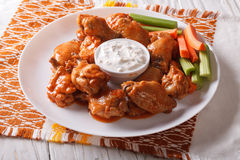 Buffalo wings with cheese sauce and celery on the table Stock Images