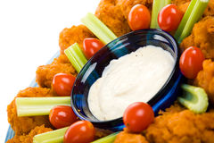 Buffalo Wings Macro. Closeup view of spicy buffalo chicken wings with ranch dressing, celery and grape tomatoes stock photos