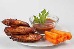 Buffalo wings set. Chicken Buffalo Wings with carrot sticks and hot tomato sauce dip over white plate stock images