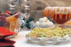 Buffet. Appetizers of shrimp cocktail, deviled eggs, fruit salad and balled pastry in crystal serving dishes on white linen with red napkins Royalty Free Stock Image