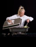 Buffet Chef. Uniformed female Chef serving from chafing tray on buffet table Royalty Free Stock Photo