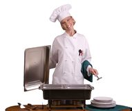 Buffet Chef with a spoon. Isolated assertive posed female Chef with a spoon standing at a buffet Royalty Free Stock Image