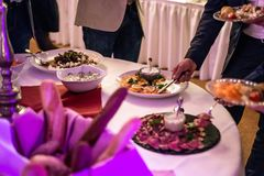 Buffet di approvvigionamento del gruppo della gente al ristorante di lusso della tavola dell'alimento con carne, pane ed insalata fotografia stock libera da diritti