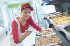 Buffet female worker servicing food in cafeteria. Worker Stock Photography