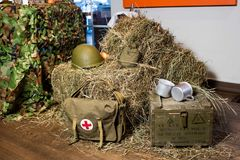 Buffet in the form of military field cuisine: hay, military helmets, first-aid kit, camouflage.  Stock Photos
