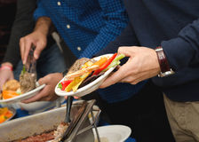 Buffet Line. A close up on a hand going through buffet of food Royalty Free Stock Images
