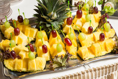 Buffet with pineapple and grapes appetizers and other fruits in restaurant Stock Image