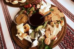 Buffet with a plate of appetizers of different varieties of cheese, fruits, sauces, crackers, embroidered cloth, Ukrainian traditi stock images