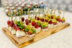 The buffet at the reception. Assortment of canapes on wooden board. Banquet service. catering food, snacks with cheese, jamon and royalty free stock photos
