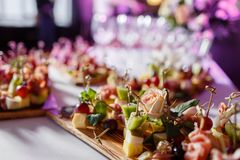 The buffet at the reception. Assortment of canapes on wooden board. Banquet service. catering food, snacks with cheese royalty free stock images