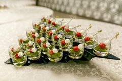 The buffet at the reception. Glasses of wine and champagne on background. Assortment of canapes in glass cups. Banquet service. royalty free stock photography