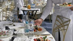 Buffet restaurant and hotel. Catering service waiters put plates with dishes on the guests table at a wedding or seminar stock video footage