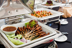 Buffet with Skewered and Grilled Meat, Satay. Buffet settings Grilled skewered meat (satay) on a chaffing dish Royalty Free Stock Images