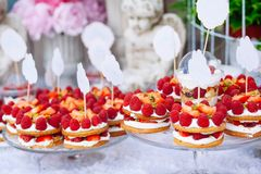 Buffet with sweets. Cakes with raspberries. Sweet table for banquets, weddings, parties royalty free stock image