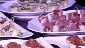 Buffet table with different dishes: canapés, tartlets, snacks stock footage