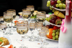 The buffet table with fruits and alcohol are near house.  Stock Photo