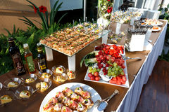 Buffet table full of food in small dishes and a fruit platter. Buffet table full of food in small serving dishes and a fruit platter Stock Photography