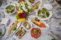 Buffet table of reception with cold snacks, meat, salads and fruits royalty free stock photography
