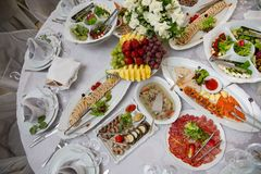 Buffet table of reception with cold snacks, meat, salads and fruits royalty free stock photo
