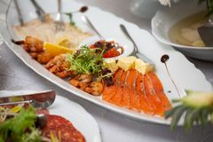 Buffet table of reception with cold snacks, shrimp, fish, caviar royalty free stock photos