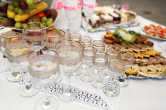 The buffet table with snacks and alcohol are near house.  royalty free stock images