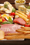 Buffet of various types of cheese and appetizers set Stock Images