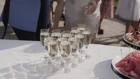 Buffetlijst met glazen champagne, fruit en canapes De vrouw neemt een glas champagne en een snack van de lijst stock footage