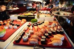 Buffett matställe Händer som upp väljer sushi- och fiskspecialiteter i b arkivfoto