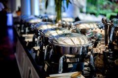 Buffettisch mit Reihe von Lebensmittel-Service-Dampf-Wannen Stockbild