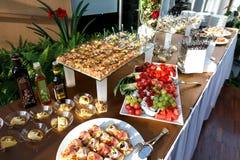 Buffettisch voll des Lebensmittels in den kleinen Tellern und in einer Fruchtservierplatte Stockfotografie