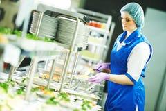 Buffetvrouwelijke werknemer die voedsel in cafetaria onderhouden stock foto