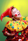 Buffoon. Boy dressed buffoon (Harlequin / clown) on a bright background stock photos