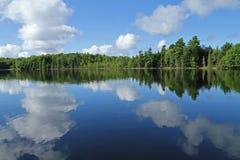 Bufiaste chmury Odbijać w jeziorze Zdjęcia Stock