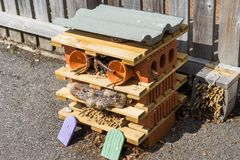 Bug hotel or house on a tarred surface. Bug or insect habitat or hotel on a tarred surface with fairy doors at the bottom to attract all creatures and Royalty Free Stock Photo