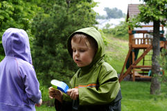 Bug  Hunt. A young boy looking for bug in the rain with his sister in the background Royalty Free Stock Photography