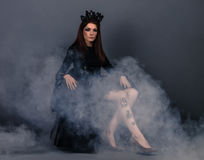 Bug queen woman with crown wearing black dress with dress sitting Stock Images