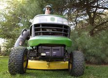 Bug's-Eye View of Man on Riding Lawnmower. White male on riding tractor-style lawn mower.  The image is taken from down on the ground in front of the mower Royalty Free Stock Image