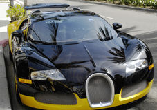 Bugatti closeup on road. Stylish Bugatti car on Rodeo Drive in Beverly Hills, California. Image taken as a closeup. The luxury car is painted in black and yellow Stock Photography