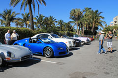 Bugatti veyron parked among other cars. Bugatti veyron in line up. parked among luxury cars. sunny day with onlookers about Stock Photo