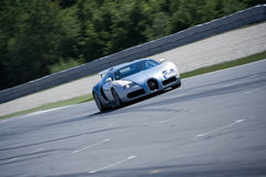 Bugatti Veyron sur le circuit pilotant à travers images stock
