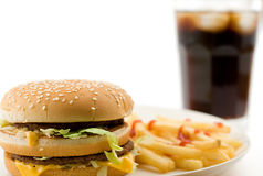 Buger and fries. Cheeseburger, soda drink and french fries, shallow DOF, shot on white Royalty Free Stock Photo