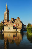 Bruges architecture - the Church of Our Lady tower. The Church of Our Lady tower reflected in the water of the Bruges channel Royalty Free Stock Photo