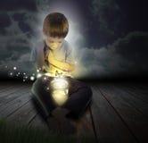 Bugga pojkebarnet med den glödande fjärilen på natten arkivbilder