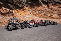 Buggies in front of a wall of rock Stock Photos